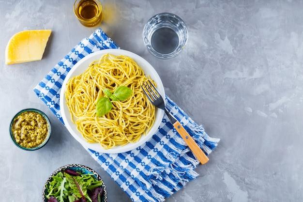 Italienische pasta mit sauce pesto und salat aus grüns mischen. spaghetti mit pesto-sauce und frischem basilikum auf grauem hintergrund. platz kopieren. ansicht von oben