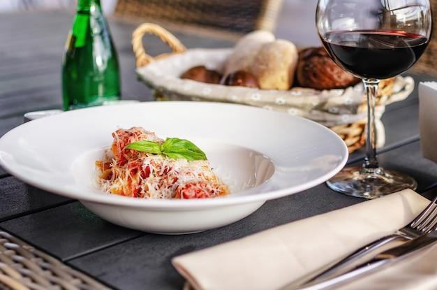 Italienische pasta mit tomaten, käse und einem zweig basilikum