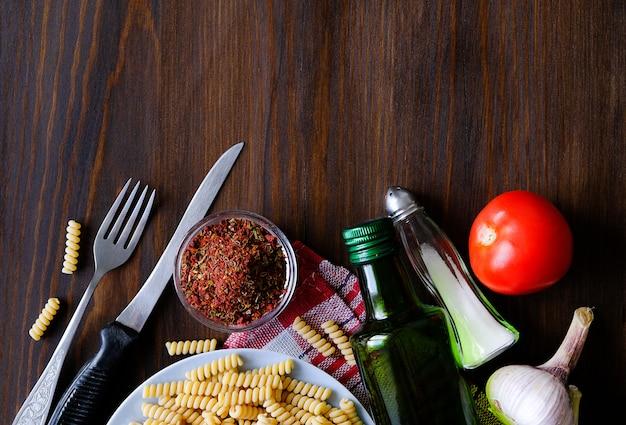 Italienische pasta, olivenöl, gewürze auf einem dunklen holztisch