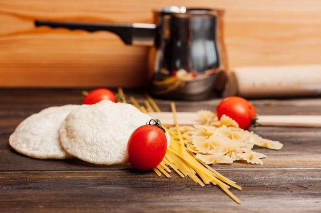 Italienische pasta pasta kirschtomaten, die holztisch kochen. hochwertiges foto