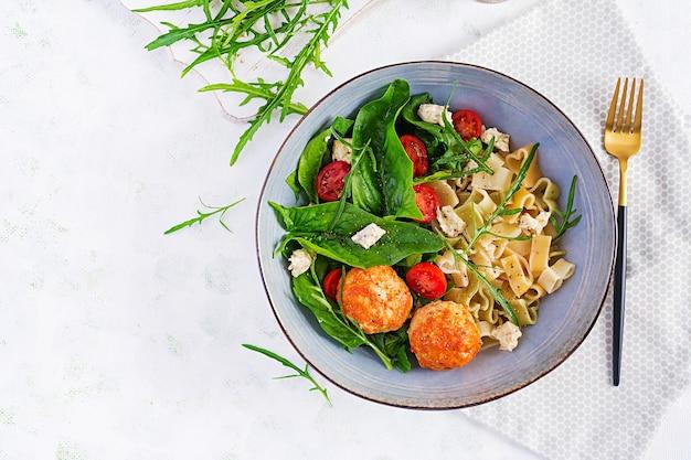 Italienische pasta. pasta mit fleischbällchen, käse und frischem salat