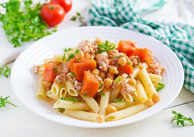 Italienische pasta, penne mit hackfleisch, kichererbsen und kürbis.