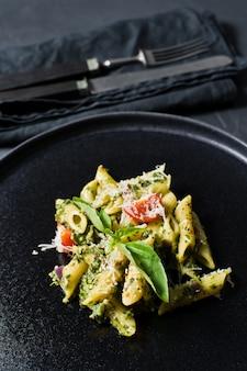 Italienische pasta penne mit spinat, kirschtomaten und basilikum.