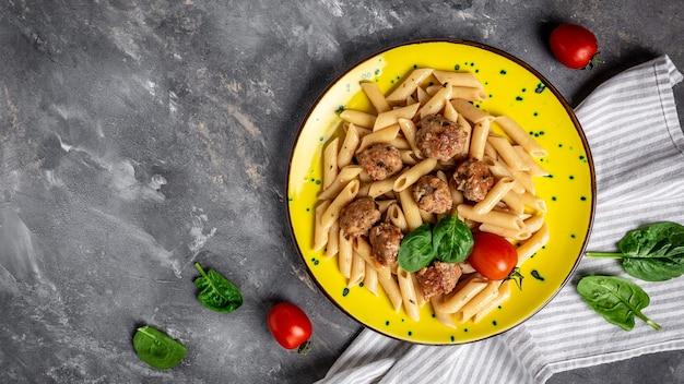Italienische pasta. penne pasta mit fleischbällchen auf einem gelben teller und einer grauen oberfläche