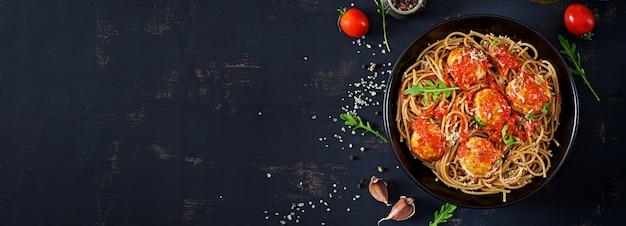 Italienische pasta. spaghetti mit fleischbällchen und parmesan in schwarzer platte auf dunklem rustikalem holztisch. abendessen. draufsicht. slow-food-konzept
