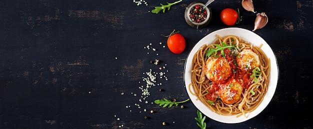 Italienische pasta. spaghetti mit fleischbällchen und parmesankäse in der schüssel auf dunklem rustikalem holztisch. abendessen. draufsicht. slow-food-konzept