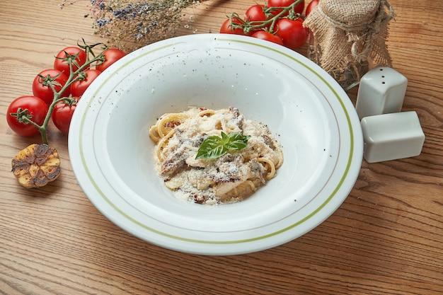 Italienische pasta spaghetti mit huhn und pilzen, parmesan, serviert in einem weißen teller auf einem holztisch. italienische küche