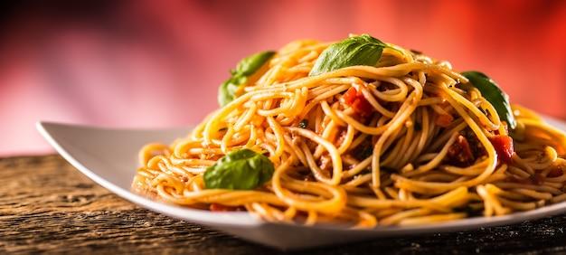 Italienische pasta spaghetti mit tomatensauce basilikum und parmesankäse in weißer platte.