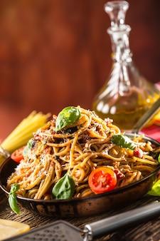 Italienische pasta spaghetti mit tomatensauce, olivenöl, basilikum und parmesankäse in einer alten pfanne.