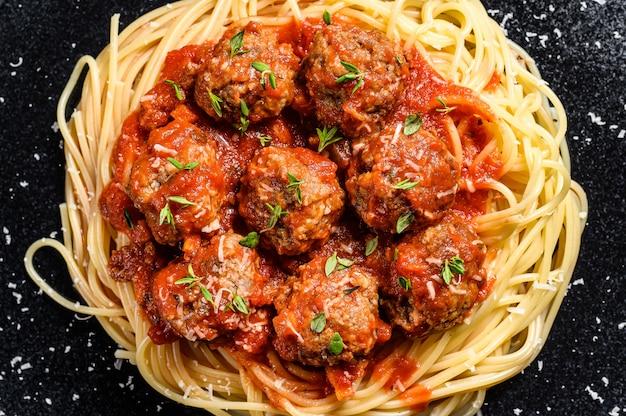 Italienische pasta spaghetti mit tomatensauce und fleischbällchen. schwarzer hintergrund. draufsicht