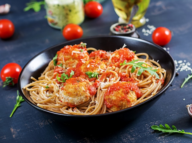 Italienische pasta. spaghettis mit fleischklöschen und parmesankäseparmesankäse im schwarzblech auf dunklem rustikalem hölzernem hintergrund. abendessen. slow-food-konzept