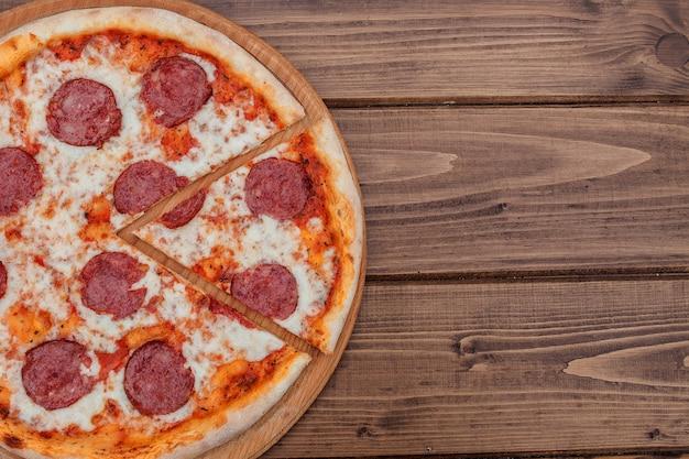 Italienische pepperonipizza mit salami auf dunkler draufsicht des holztischs. italienisches traditionelles essen. beliebtes street food