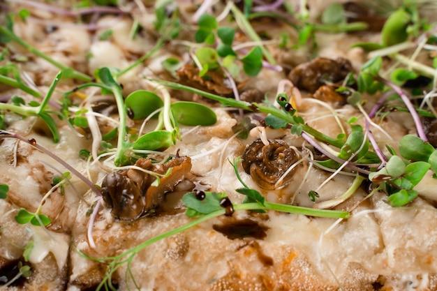Italienische pinsa romana mit französischen schnecken traubenschnecken auf dunklem hintergrund nahaufnahme. pinsa mit schnecke, käse, mikrogrün. italienische gourmetküche.