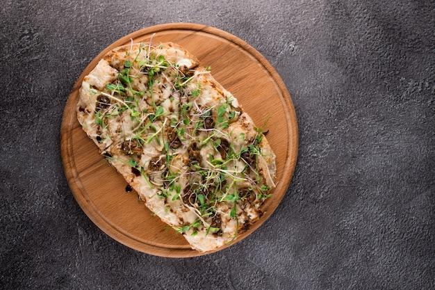 Italienische pinsa romana mit französischen schneckentraubenschnecken auf dunklem hintergrund. pinsa mit schnecke, käse, mikrogrün. italienische gourmetküche.