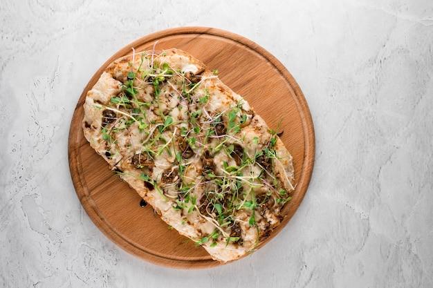 Italienische pinsa romana mit französischen schneckentraubenschnecken auf weißem hintergrund. pinsa mit schnecke, käse, mikrogrün. italienische gourmetküche.