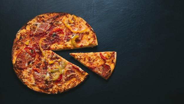 Italienische pizza auf einem schwarzen hintergrund mit draufsicht. platz für text