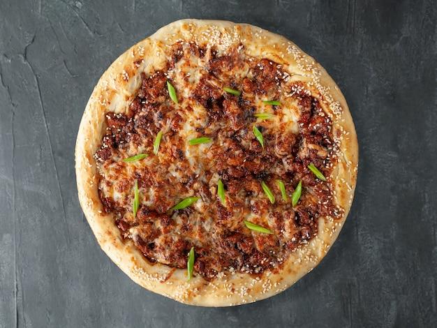 Italienische pizza. geräuchertes hühnchen, mozzarella-käse, sulguni, tomatensauce, gewürze und frühlingszwiebeln. breite seite. sicht von oben. auf grauem betonhintergrund. isoliert.