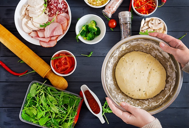 Italienische pizza. hände, die mit der teigvorbereitungspizza oder -torte machen bestandteile auf tabelle arbeiten.