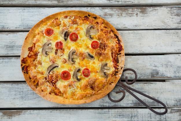 Italienische pizza in einer pfanne auf einem holzbrett