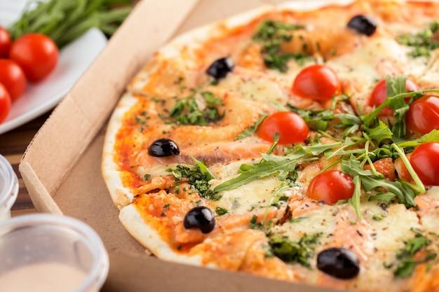 Italienische pizza mit dünner kruste und lachs in pappe