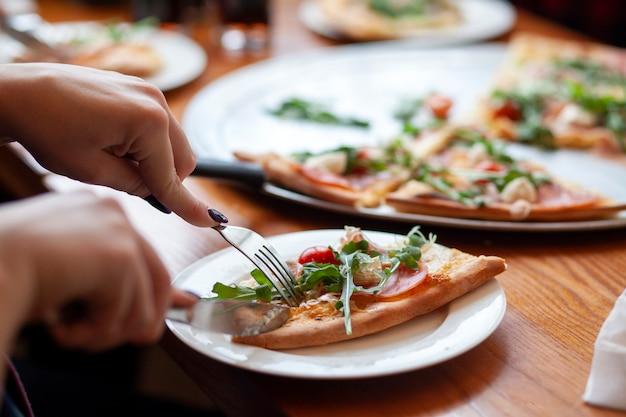 Italienische pizza mit einer gabel und einem messer gegessen