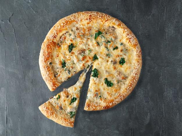 Italienische pizza. mit hühnchen, spinat und champignons. in cremiger sauce, mit mozzarella und sulguni-käse. von der pizza wird ein stück abgeschnitten. sicht von oben. auf grauem betonhintergrund. isoliert.