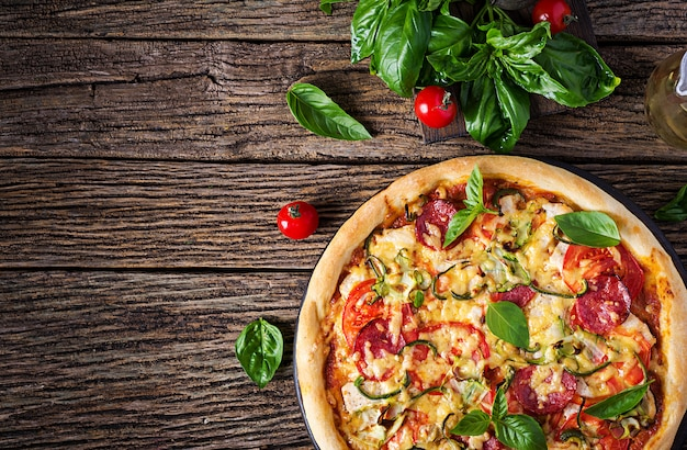 Italienische pizza mit huhn, salami, zucchini, tomaten und kräutern