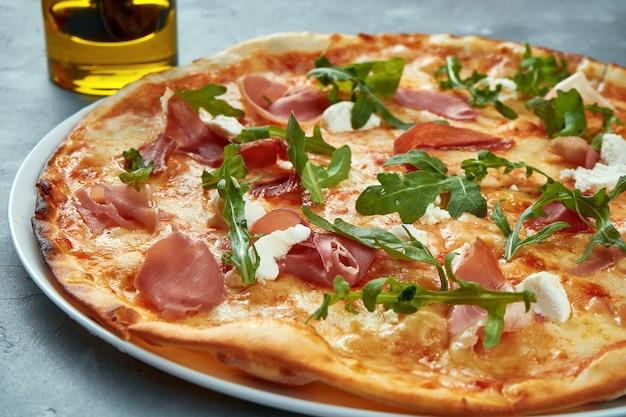 Italienische pizza mit jamon, rucola und frischkäse auf einem grau