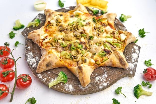 Italienische pizza mit meeresfrüchten, muscheln, garnelen, frischen kräutern, zwiebeln, mozzarella und pilzen auf einem holzbrett