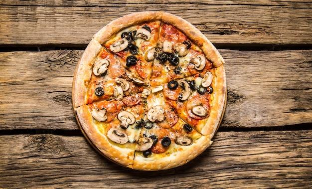 Italienische pizza mit oliven und speck.