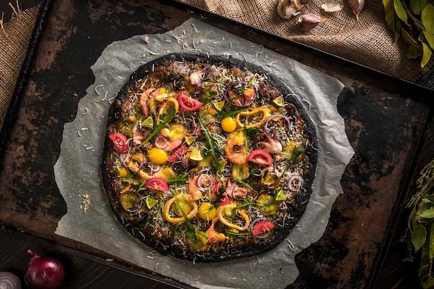 Italienische pizza mit schwarzem teig und meeresfrüchten auf einem backblech aus dem ofen. darauf lagen tintenfisch, garnelen, tintenfisch, zwiebeln, tomaten. tintenfischtinte