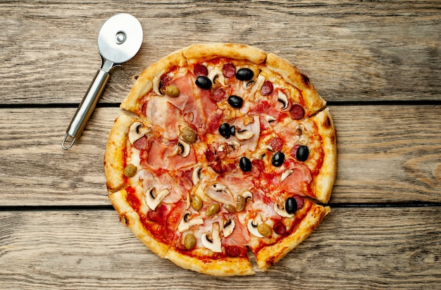 Italienische pizza mit speck, pilzen, oliven, tomaten auf einem holzhintergrund