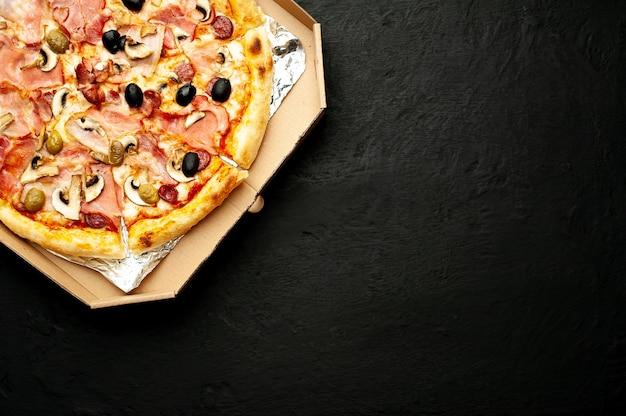 Italienische pizza mit speck, pilzen, oliven, tomaten auf einem schwarzen betonhintergrund mit kopienraum für ihren text
