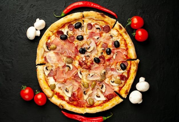 Italienische pizza mit speck, pilzen, oliven, tomaten auf einem schwarzen betonhintergrund