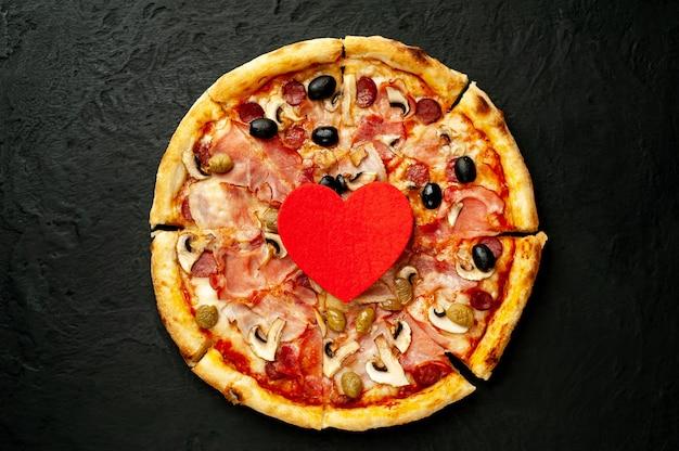 Italienische pizza mit speck, pilzen, oliven, tomaten mit roten herzen für valentinstag auf schwarzem betonhintergrund