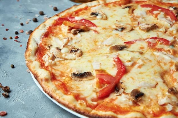 Italienische pizza mit speck, pilzen, tomaten, geschmolzenem käse auf einem grau