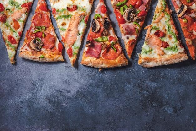 Italienische pizza mit tomaten, pilzen, speck, lachs und pfeffer. lieferservice essen auf schwarzem hintergrund