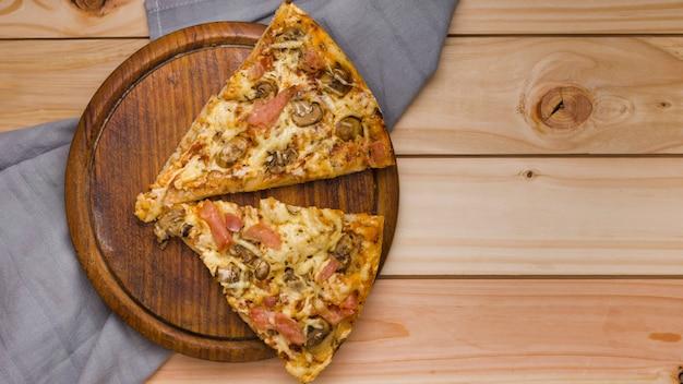 Italienische pizza mit zwei käsescheiben auf kreisförmigem hölzernem behälter über der tabelle