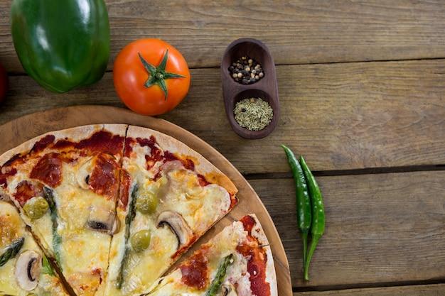 Italienische pizza serviert in einem pizzatablett mit zutaten und gemüse