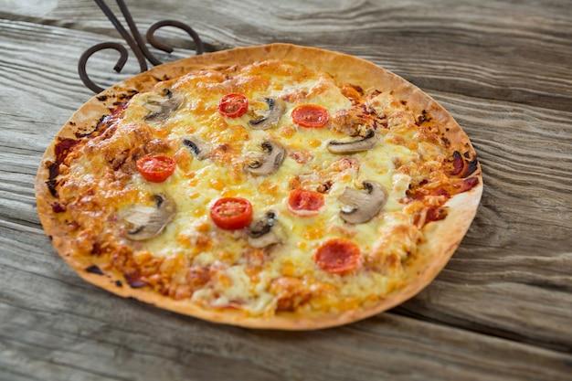 Italienische pizza serviert in einer pfanne auf einem holzbrett