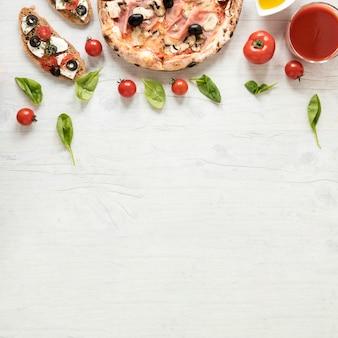 Italienische pizza und bruschetta mit bestandteil über hölzernem strukturiertem hintergrund