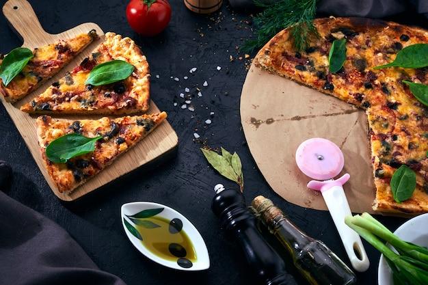 Italienische pizza und pizza, die zutaten auf dunklem hintergrund kochen