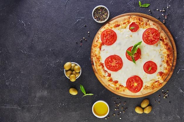 Italienische pizza und zutaten zum kochen auf einem schwarzen betonhintergrund. tomaten, oliven, basilikum und gewürze. kopieren sie platz für text.