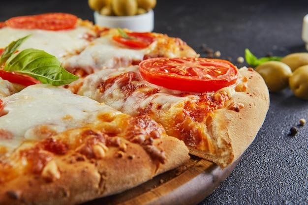 Italienische pizza und zutaten zum kochen auf einem schwarzen betonhintergrund