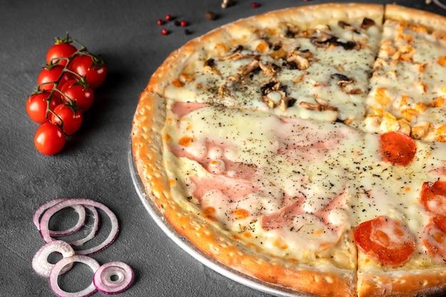 Italienische pizza vier jahreszeiten mit käse, schinken, pilzen, tomaten, zwiebeln, peperoniwurst auf einem grauen tisch, nahaufnahme