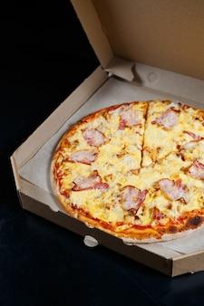 Italienische pizzalieferung. köstliches ofengebackenes pizzeriagericht mit mozzarella, parmesan und käse, geliefert in einem karton. leckeres fast food zum mitnehmen, das zum abendessen im ofen zubereitet wird.