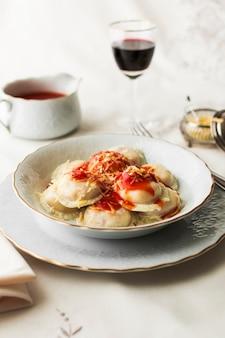 Italienische ravioli-nudeln mit würziger tomatensauce und käse in der schüssel