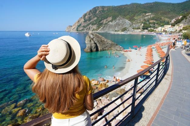 Italienische riviera. hübsches mädchen mit hut an der promenade mit blick auf das dorf monterosso al mare auf cinque terre, italien?