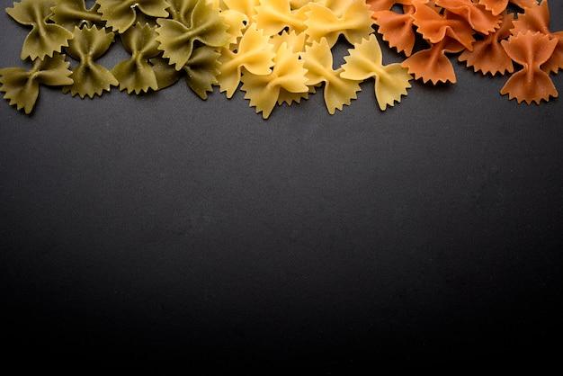 Italienische rohe frische fliegenteigwaren über schwarzem hintergrund mit kopienraum für das schreiben des textes
