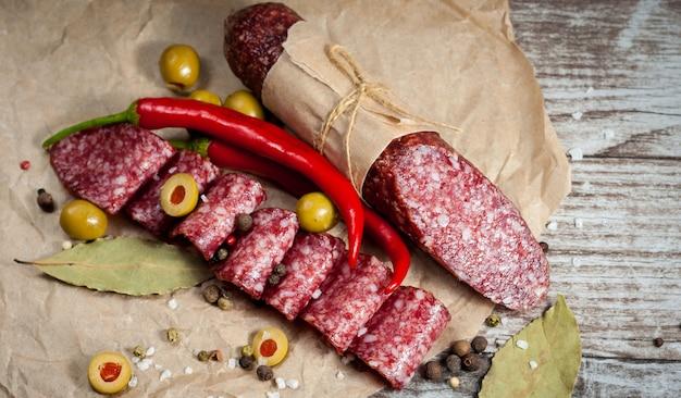 Italienische salami mit oliven und gewürzen auf hölzernem hintergrund